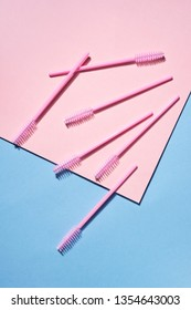 Creative concept beauty photo of lashes extensions brush on pink blue background.