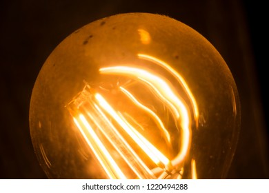 creative concept for electrical revolution or elecrification starting with Thomas Edison as an now old idea represented by yellow, orange light bulb with dust on surface