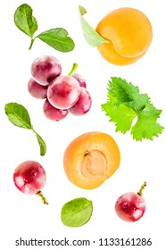 Creative concept with flying apricots and grapes with leaves. whole and halves of apricots and grapes with green leaves falling isolated on white background