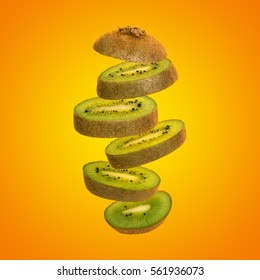Creative concept with flying kiwi. Sliced kiwi isolated on yellow background. Levity fruit floating in the air