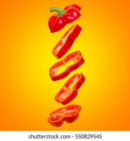 Creative concept with flying orange paprika. Sliced floating bell pepper on an orange background. Levity  vegetable. Capsicum with water drops