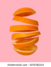 Creative concept with Flying orange. Sliced orange flies isolated on pink background. Levity fruit floating in the air.