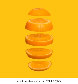 Creative concept with flying orange. Sliced orange on yellow background. Levity fruit floating in the air