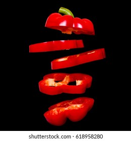Creative concept with flying red paprika. Sliced floating pepper isolated. Levity capsicum vegetable isolated on black background