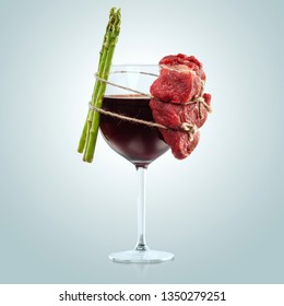 Creative concept health food photo of glass of wine alcohol drink beverage spirits meat and asparagus tied with the rope on blue background.