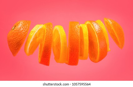 creative concept of levity fruits floating in the air. slices of lemon and orange isolated on pink background