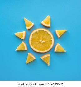 Creative concept made from sliced orange like sun. Blue background. Sunny weather theme. Flat lay.