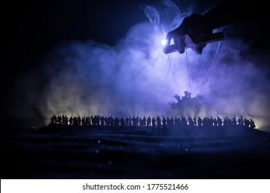 Creative concept of manipulation with coronavirus. Crowd looking on big Corona virus miniature. The hand controls the Covid19 miniature with strings on a dark foggy background. Selective focus
