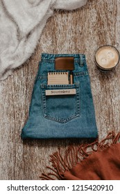 Creative concept of November begining. Notebook and a pen in a jeans pocket beside cup of coffee and warm autumn clothing