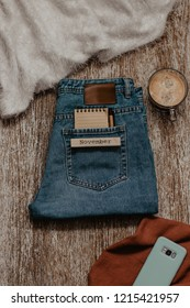 Creative concept of November begining. Notebook and a pen in a jeans pocket beside cup of coffee,smartphone and warm autumn clothing