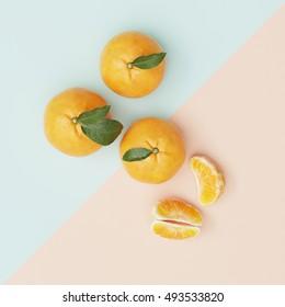 Creative Concept.  Orange on light blue cross yellow pastel background, top view.