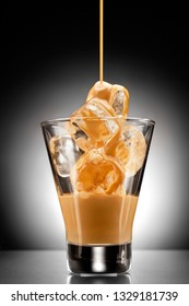 Creative concept photo of alcohol spirits drink beverage cocktail Irish cream liqueur pouring into a glass full of ice