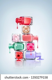 Creative concept photo of beauty product nail polish dripping from stacked bottles on white background.