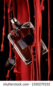Creative concept photo of beauty product luxury male perfume fragrance eau de toilette lotion scented water cologne in a transparent spray bottle and flowing red paint.