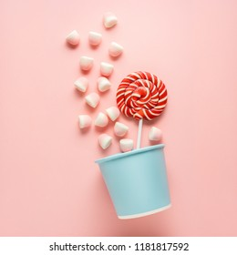Creative concept photo of candies in basket on pink background.