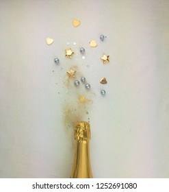 Creative concept photo of champagne bottle with confetti on  background.
