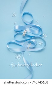 Creative concept photo of christmas tree made of ribbon and  jewellery on blue background.