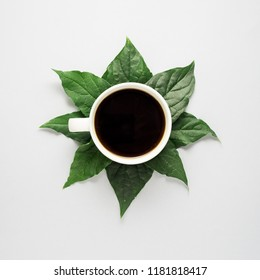 Creative concept photo of coffee cup with leaves on grey background.