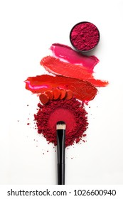 Creative concept photo of cosmetics swatches  beauty products lipstick eyeshadow and brush  on white background.
