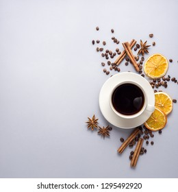 Creative concept photo of cup of coffee with beans cinnamon and dry oranges on grey background.