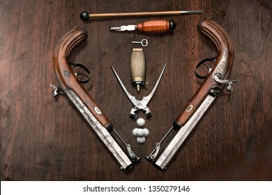Creative concept photo of duel pistols guns became a an indispensable attribute of high ranking persons like at the end of 18th century on brown wooden background. Handmade in Germany at 1850.