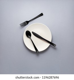 Creative concept photo of fork spoon and knife laying on plate on grey background.