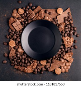 Creative concept photo of frame made of chocolate with plate on black background.