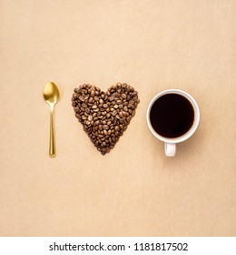 Creative concept photo of heart made of coffee with cup and spoon on brown background.