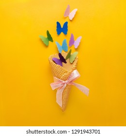 Creative concept photo of ice cream waffle cone with paper butterflies on yellow background.