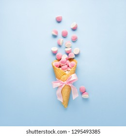Creative concept photo of ice cream waffle cone with jelly candies on blue background.