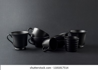 Creative concept photo of kitchenware, painted cups and mugs on black background.