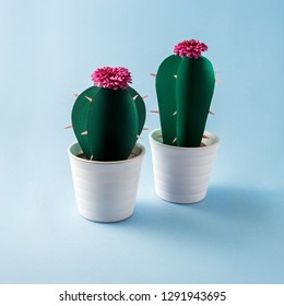 Creative concept photo of paper cactus flowers in pots on blue background.