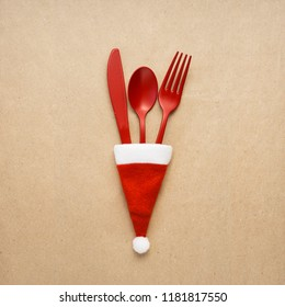 Creative concept photo of tableware christmas hat in on brown background.