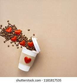 Creative concept photo of take away coffee cup with hearts on brown background.