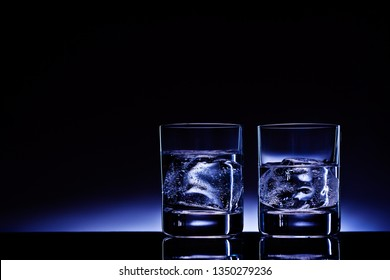 Creative concept photo of two glasses of vodka alcohol spirits with ice cubes against the background of deep blue glow.