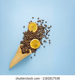 Creative concept photo of waffle cone filled with coffee and oranges on blue background.
