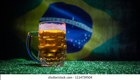 Creative concept. Pint of fresh beer on grass with blurred flag of Brazil on background or Glass of lager beer ready for drink. Copy space. Selective focus
