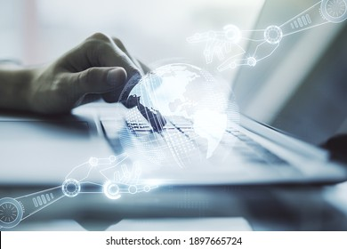Creative concept of robotics technology with globe sketch and hands typing on laptop on background. Robot development and automation concept. Multiexposure