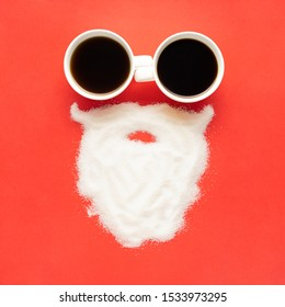 Creative concept still life christmas new year holiday photo of espresso coffee cups mugs drink beverage with santa clause face beard made of sugar on red background.