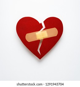 Creative concept valentines day photo of paper broken heart  with plaster bandage on white background.