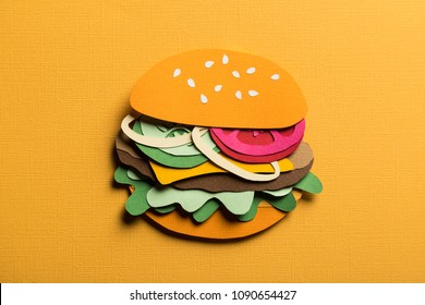 Creative conceptual art still life. Paper craft hamburger with cheese tomatoes and onions on a yellow background. Stylish composition cut out from colored paper. Illustrative close-up collage.