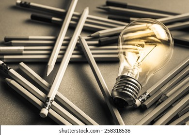 Creative content  writing, light bulb and many pencils on the table
