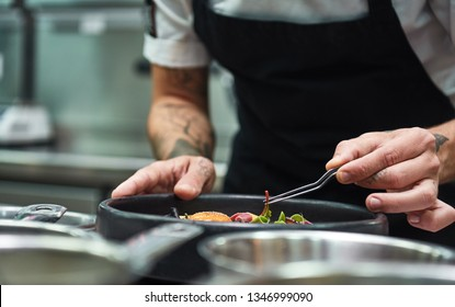 Creative Cooking. Cropped image of chef hands garnishing Pasta carbonara in a restaurant kitchen.