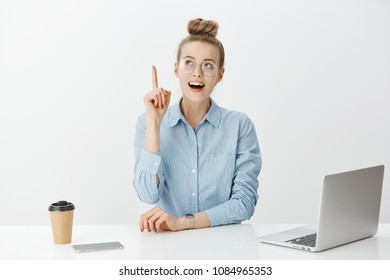 Creative coworker wants add suggestion. Smart good-looking european entrepreneur in glasses, raising index finger, looking up with smile while having idea or plan, sitting near laptop and smartphone.