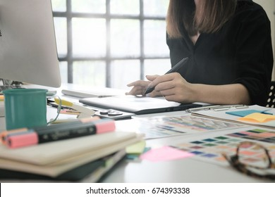 Creative or creator woman working on designer desk with graphic design job.