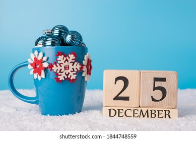 Creative cup for coffee full of small toy nice beautiful baubles ans wooden cubes calendar with Christmas day date standing in fluffy white snow blue sly space on background