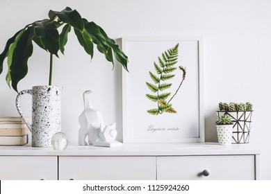Creative cupboard with mock up poster frame, cat figure, tropical leaf and plant. White wall background. Modern scandinavian interior.