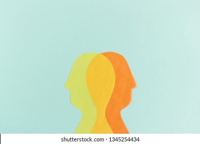 Creative cutout silhouette heads of transparent colorful paper looking oppositely in contrary directions