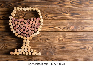 Creative design of a full wineglass made with corks from red and white wine bottles on a rustic wood background with copy space