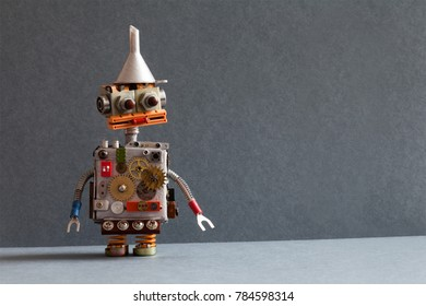 Creative design robot toy with metal funnel hopper, cogs wheels gears silver metallic body. gray background. Copy space.